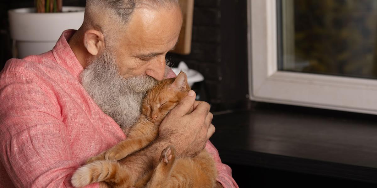 Un signore anziano bacia il suo gatto